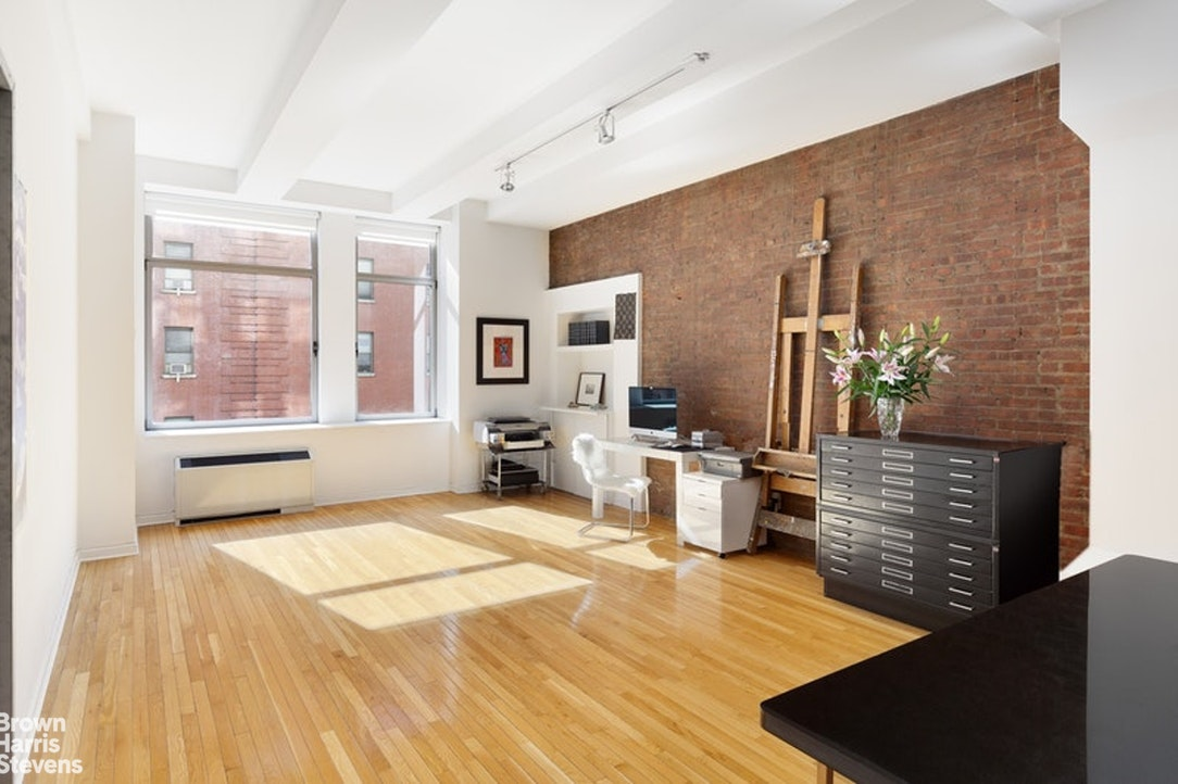 Sun-flooded all day from extra-large south facing windows in both rooms, a true loft with exposed brick walls, long oak plank floors, 11' ceilings, and tons of storage this unique 1.5 bedroom apartment is not to be missed! Enter the voluminous 1140SF apartment from a long entry hall, with internal den or home office off to the right that can easily fit a king sized bed and furniture. There are floor to ceiling closets along one wall, and one of two full bathrooms across the entry. The open kitchen has stainless steel appliances, tons of cabinetry, dark stone counters, and an island with counter seating. The living space makes for great entertaining and can easily accommodate a dining table for up to 10 people and a full living room set up with multiple couches and chairs. The master bedroom features upgraded recessed lighting, mahogany engineered wood floors, custom below window casings for HVAC, a large closet, and en-suite five fixture master bathroom with designer lighting and bespoke wallpaper. This apartment is located at the end of the hall for ultimate privacy. Additionally a coveted basement storage unit is included with this sale. There is currently a assessment of $177.73.Built in 1908 The Chelsea Mercantile is a full service doorman building, offering the ultimate convenience of Whole Foods on the lobby level. There is a gym, valet service, concierge, play room, and 10,000sf landscaped roof deck with views across the city. Direct access to a public parking garage from the lobby is available. The building is meticulously maintained with a brand new renovated lobby and four elevator banks. At the crossroads of Downtown and Midtown, with easy access to the 1,C,E,F,M,Q, and R trains.