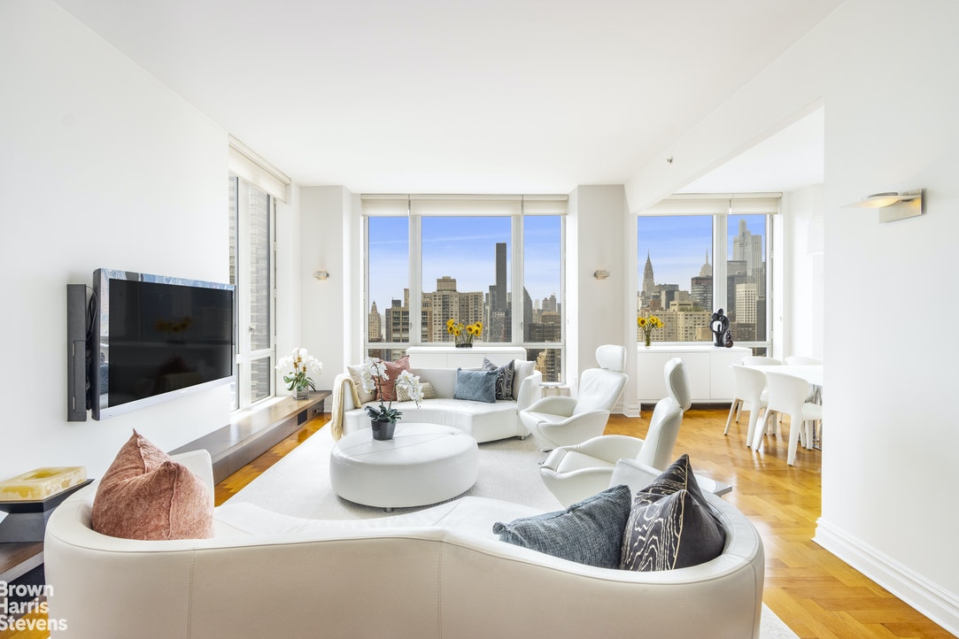 """NEW TO MARKET!! Perched on the 30th floor of the luxurious Bridge Tower Place Condominium, Residence 30A at 401 East 60th Street is a gorgeous 6-room, 3-bedroom, 3.5-bathroom home with soaring ceilings and open river, bridge and city views spread across approximately 2,000 square feet.The New York City skyline greets you through enormous floor-to-ceiling windows as you pass through the elegant entry foyer and into an exquisite entertaining room with hardwood herringbone floors and three exposures, South, East and West, framing spell-binding sunsets and dramatic vistas of the Chrysler Building and Empire State Building and beyond. The living and dining rooms sit side-by-side, creating the perfect setting for grand entertaining or enjoying an intimate dinner alone.A large windowed kitchen lies directly North of the dining room and features all stainless steel appliances including a 4-burner gas range and oven, a 36"""" refrigerator with double freezer drawer, a dishwasher by Bosch as well as a double sink with garbage disposal. The kitchen is finished with abundant maple wood cabinetry, sleek black granite countertops and granite floors. Rounding out the entertaining wing is a conveniently placed powder room for guests just off of the foyer.Three bright and well-proportioned bedrooms occupy the South end of this residence, each with a windowed en-suite bathroom finished in marble and customized storage. Each bedroom offers dual exposures with postcard river and bridge views in the primary and second bedrooms. The massive primary suite is discreetly tucked away in its own corner of the apartment, with a five-fixture en-suite bathroom featuring an array of custom closets and a double vanity, soaking tub and stall shower.Additional luxuries include an in-unit washer/dryer, glorious hardwood floors throughout, through-wall air conditioning and a private storage unit.Bridge Tower Place Condominium was built in 1999 as an amenity-rich residential enclave affording its resident"""