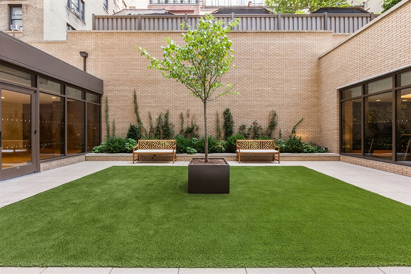 The lush central courtyard visually connects the sunlit wellness center and multipurpose sports court.